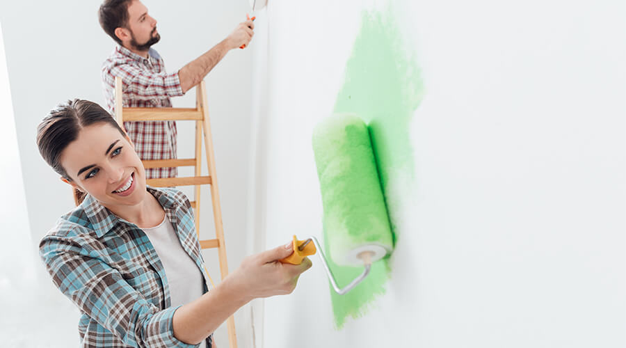 couple painting walls in house