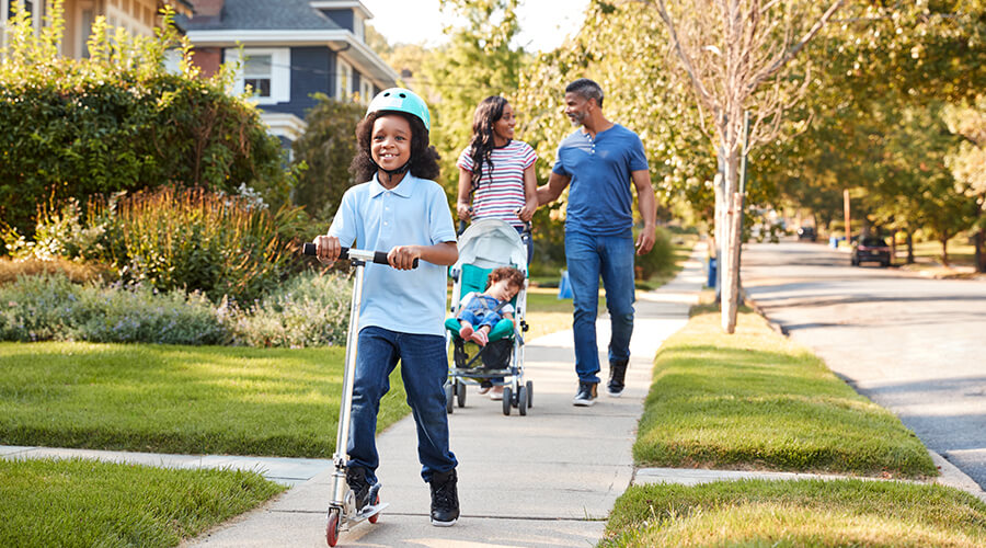 family happy walking through neighbourhood