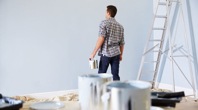 man painting and decorating room