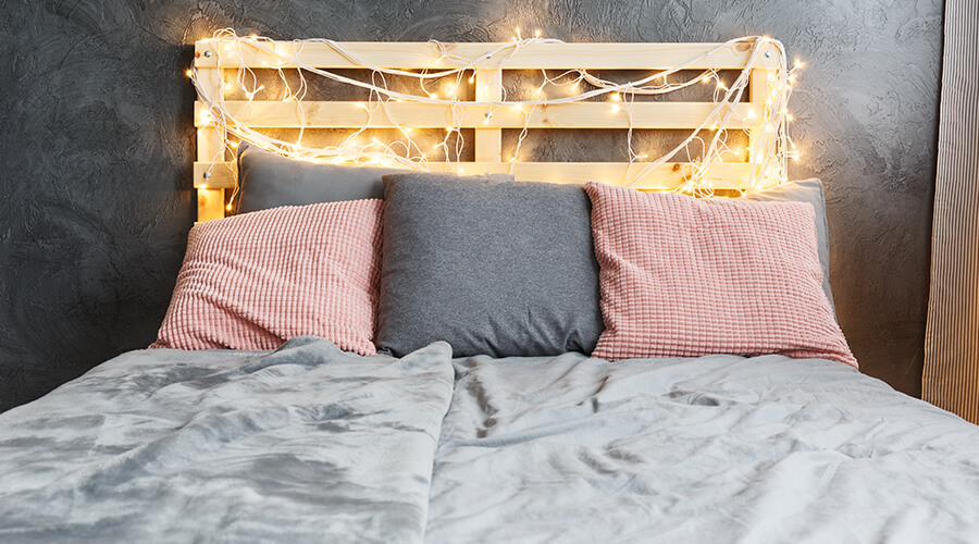 bed with fairy lights around headboard